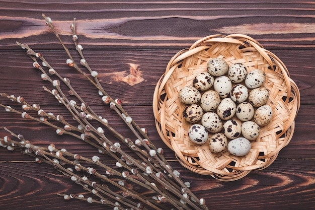 Quail eggs in a wicker straw plate and plants on dark wooden background with copy space. easter concept.