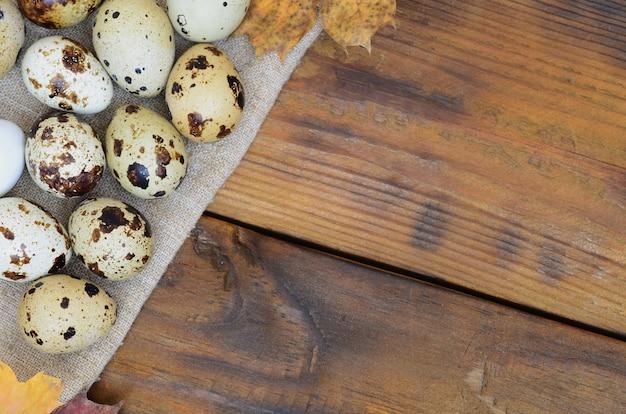 Перепелиные яйца с осенними листьями на мешковине на темно-коричневой деревянной поверхности
