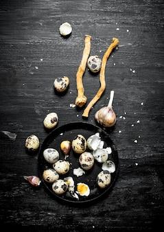 黒い木製のテーブルにニンニクと塩とウズラの卵。