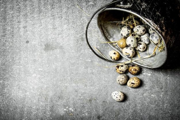 石のテーブルの上の古い鍋に干し草とウズラの卵。