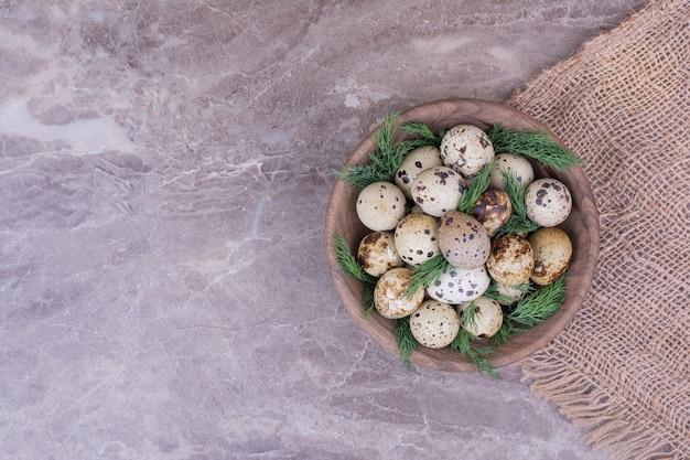木製のカップにハーブとウズラの卵。