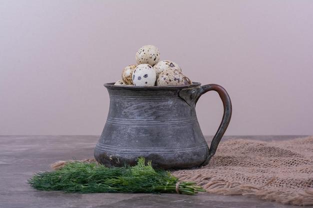 Uova di quaglia con erbe aromatiche in una tazza metallica.