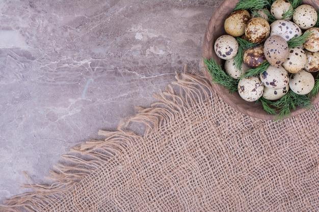 Uova di quaglia con erbe aromatiche in una tazza di legno.