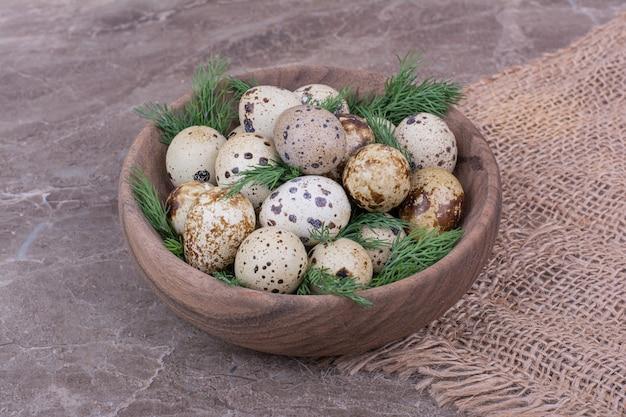 Uova di quaglia con erbe tritate in una tazza di legno