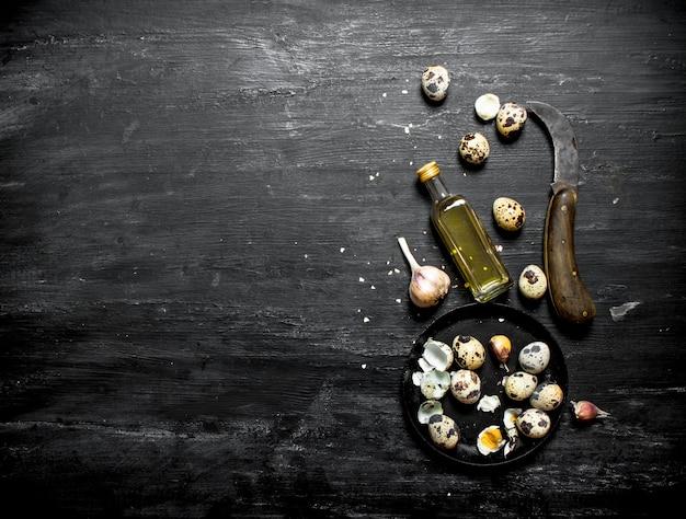 黒い木製のテーブルにオリーブオイルとニンニクとウズラの卵。