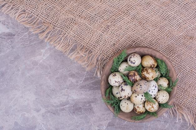 Uova di quaglia in una tazza di legno con erbe aromatiche