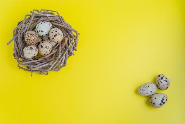 黄色の背景に卵とウズラの巣。はがきやデザインのコピースペース付きフラットレイ