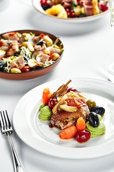 Тушеные с овощами перепела на праздничном столе с белыми скатертями, свадебный стол с перепелиными закусками.