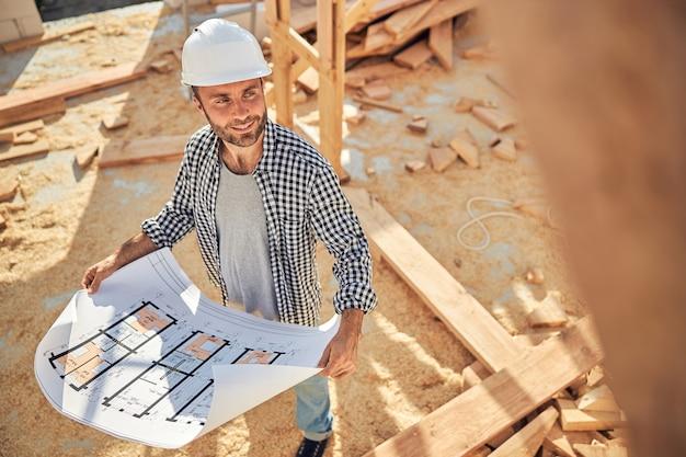 家の青写真を持つ資格のある建設現場の労働者