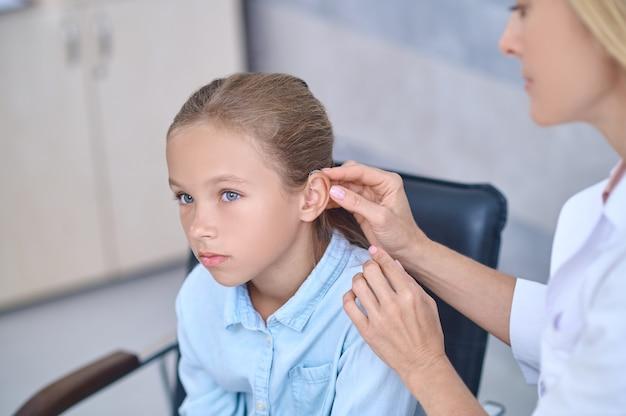 女の子の耳の後ろで補聴器を修理する資格のある医師