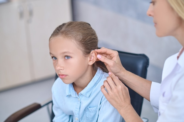 Qualified doctor fixing a deaf aid behind the girls ear