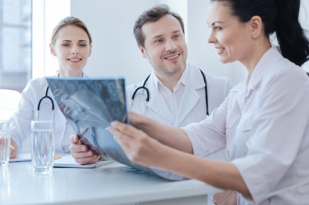 資格のある経験豊富な親切な脳神経外科医が、意見を共有し、x線写真を分析しながら、若い同僚と働き、話し合いを楽しんでいます