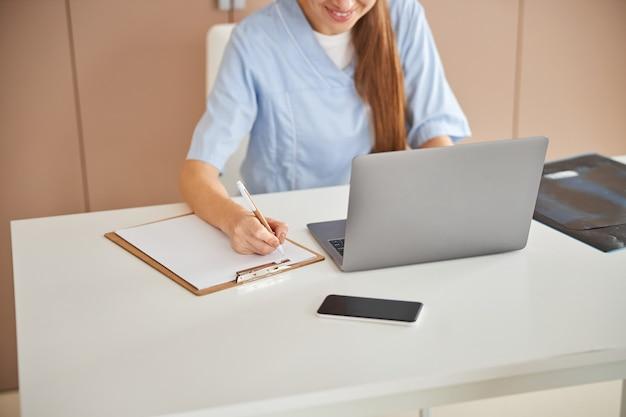 資格のある女性医師がメモを書き、笑顔
