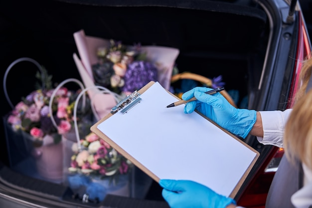 Qualified flower shop assistant taking notes about a bouquet delivery