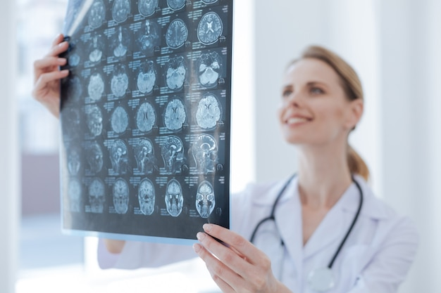 Qualified glad diligent radiologist working at the clinic while examining x ray and analyzing diagnose verdict