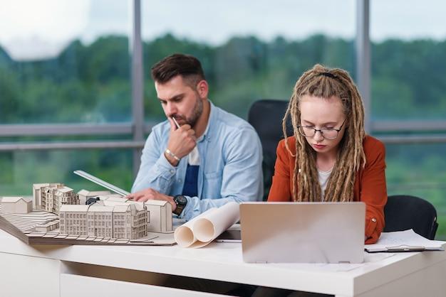 Квалифицированные и трудолюбивые креативные дизайнеры мужского и женского пола, работающие с макетами зданий.