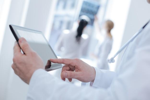 Квалифицированный задействовал умный медик, работающий в клинике и использующий планшет, в то время как его коллеги обсуждают результаты мрт-сканирования.