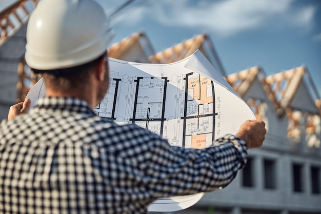 青写真を見ている建設現場の資格のある労働者