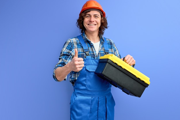 Qualified workman in overalls carrying instruments isolated over purple background