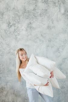 高品質の寝具。熟睡のコンセプト。笑顔の女性は枕の山を保持します。灰色のテクスチャ壁にスペースをコピーします。