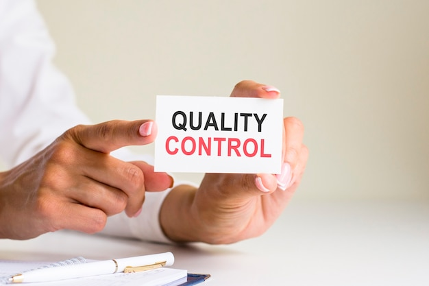 Quality control inscription on white card paper sheet in hands of woman. black and red letters on white paper. business concept, gray backgrond