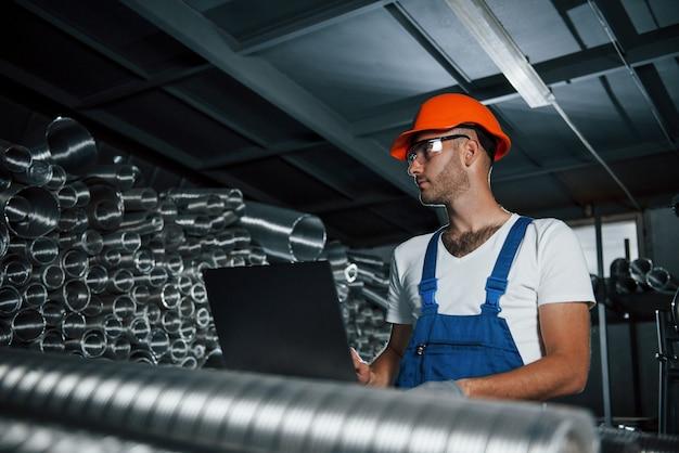 Контроль качества. мужчина в военной форме работает на производстве. современные промышленные технологии.