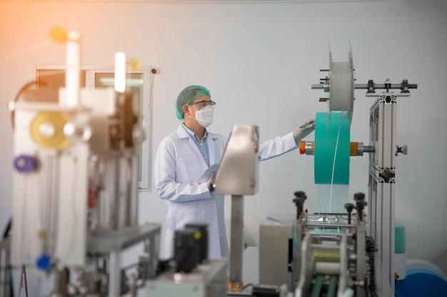 実験室で製造機械を分析する品質管理労働者。