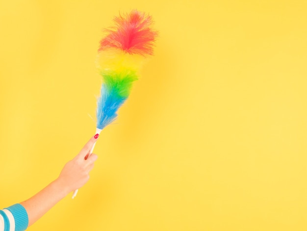 質の高い家の掃除。カラフルな羽のダスターと女性の手。黄色の背景にスペースをコピーします。