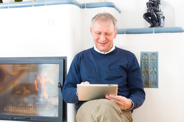 Quality of life - older man or pensioner sitting at home in front of the furnace, writing emails on the tablet computer or reading a e-book