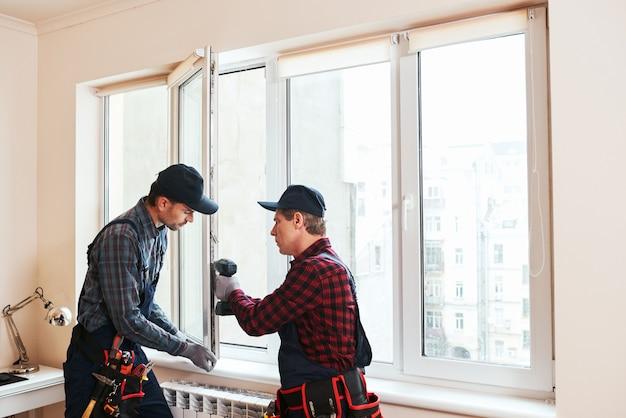 Качественные легкие строительные рабочие устанавливают новое окно в доме