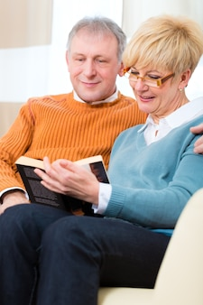 삶의 질-두 노인이 집에 소파에 앉아 아내를 포옹