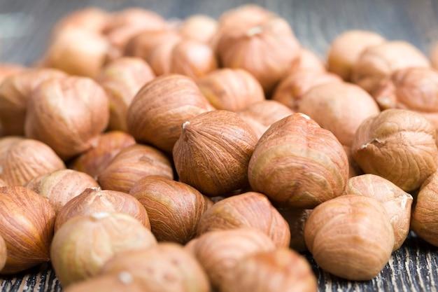 Качественные сырые орехи фундук готов к употреблению, фундук на кухонном столе во время приготовления, фундук свежий и очищенный, поверхность орехов не идеальна, крупным планом