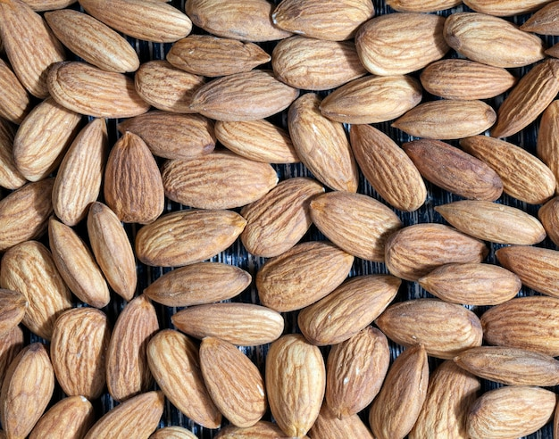 Quality raw nuts ready to eat, almonds on the kitchen table during cooking, almonds fresh and peeled, surface of the nuts is not perfect and has some natural defects due to their preparation in food