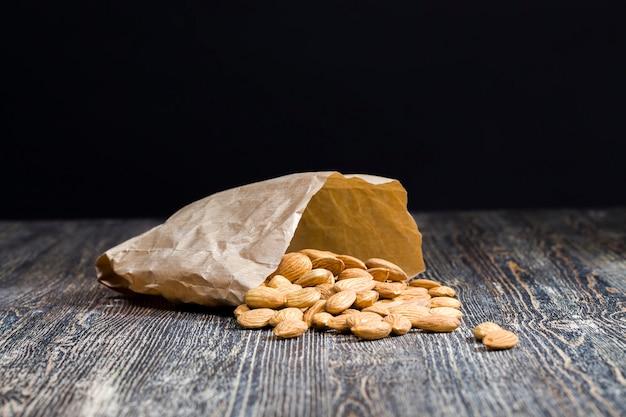 Качественные сырые орехи, готовые к употреблению, миндаль на кухонном столе во время приготовления, миндаль свежий и очищенный, крупный план, поверхность орехов не идеальная, миндаль в бумажном пакете