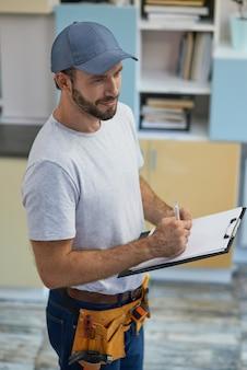실내에 서 있는 동안 클립보드에 메모를 하는 고품질 서비스 전문 젊은 수리공