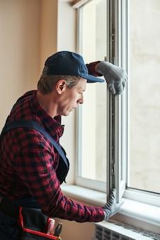 Вид сбоку качественных навыков старшего разнорабочего, устанавливающего новые окна