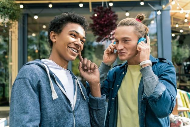 고품질 사운드. 좋은 음악을 들으면서 헤드폰을 쓰고 긍정적 인 젊은이들 프리미엄 사진
