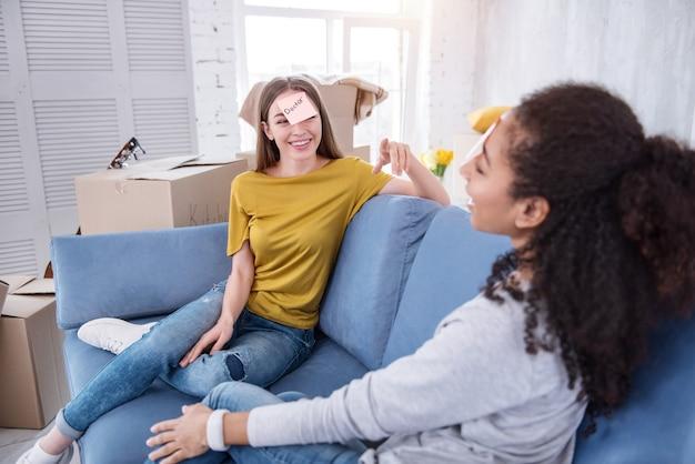 充実した時間。ソファに座って、荷物を開梱して休憩しながら面白いゲームをしている陽気な若い女の子