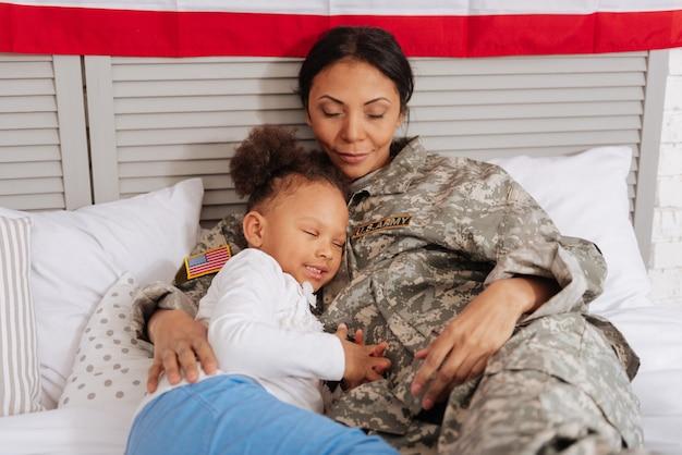 充実した時間。かわいい愛情のあるかわいい子供と彼女のゴージャスなママは、一緒にできるだけ多くの時間を過ごし、何時間も話した後、ベッドで休んでいます