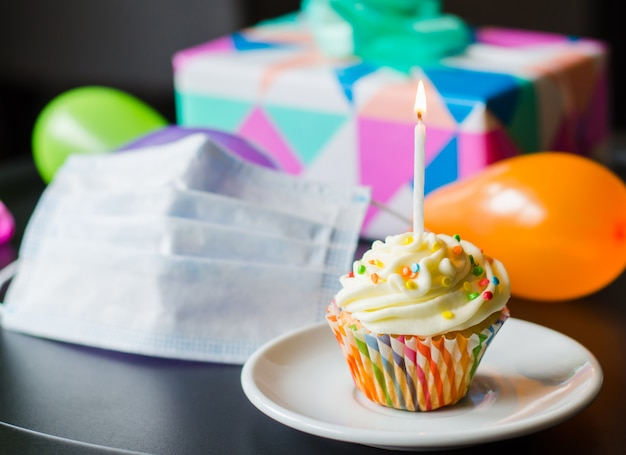 Quarantine birthday in isolation. birthday cupcake, face mask, gifts and holiday accessories.