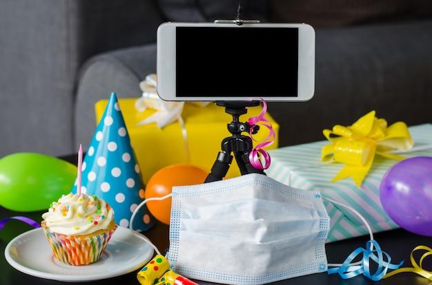 誕生日をオンラインで隔離する。スマートフォン、バースデーカップケーキ、メディシンマスク、ギフト、ホリデーアクセサリー。