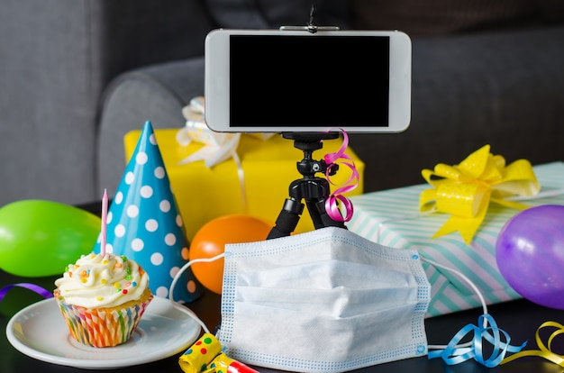 Quarantine birthday online in isolation. smartphone, birthday cupcake, medicine mask, gifts and holiday accessories.