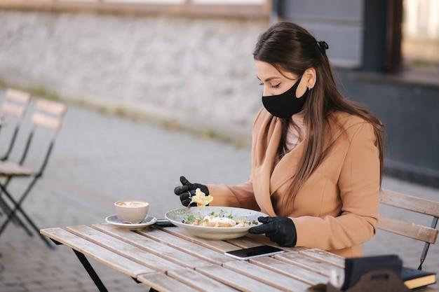 테라스에서 카페 개념 검역. 혼자 카페에 앉아 매력적인 젊은 여자.