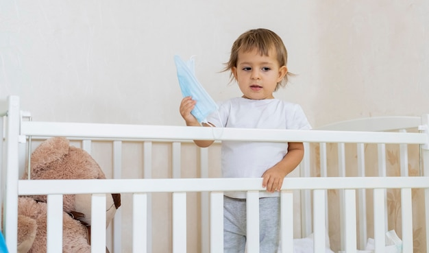 검역 코로나바이러스 코비드 전염병 개념은 작고 귀여운 심각한 아기가 집에 있는 유아용 침대에 있습니다