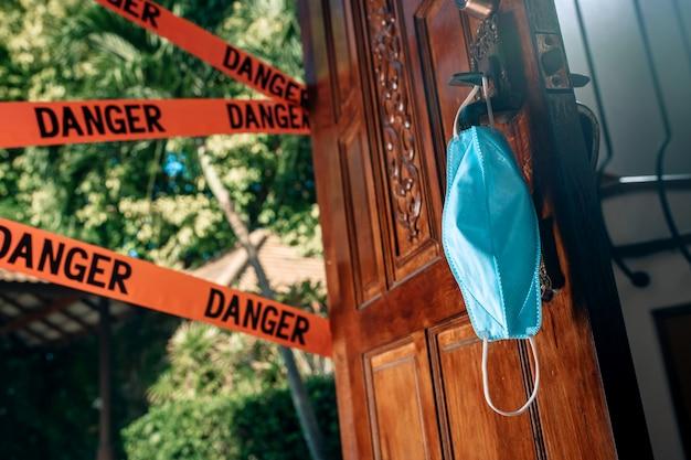Карантин. коронавирус пандемия. вход на улицу закрыт красными предупреждающими лентами - опасность. защитная маска.
