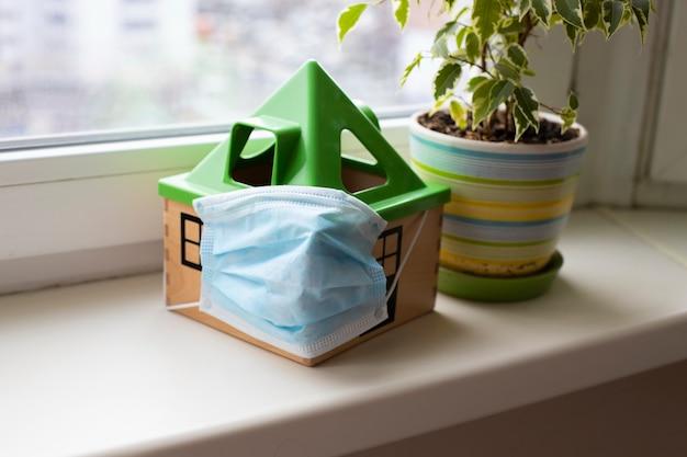 検疫コロノウイルスの概念医療マスクのおもちゃの家は花の隣の窓辺に立っています