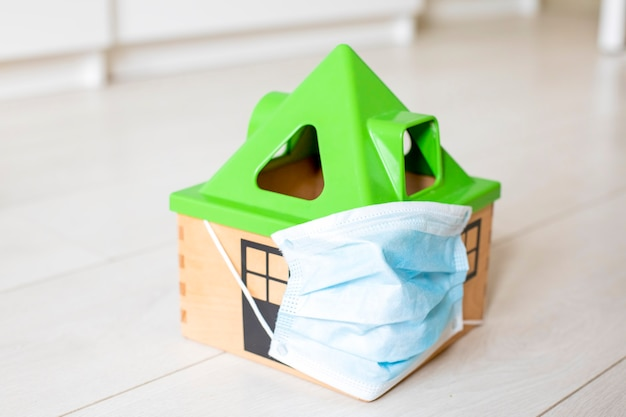 検疫コロノウイルスの概念。家の床には、医療用マスクのおもちゃの家が立っています。