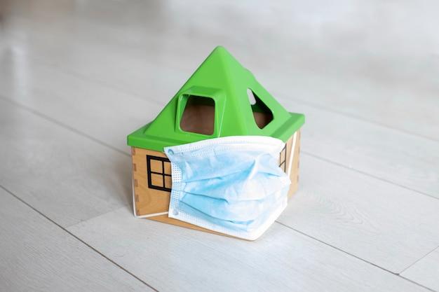 検疫コロノウイルスの概念医療マスクのおもちゃの家は白い床に立っています