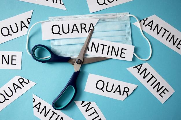 保護マスクと一枚の紙をquarantineという言葉で切るはさみ。コロナウイルスcovid-19の終わりの記号。通常の生活に戻ります。検疫制限の緩和。分離は終わりました。