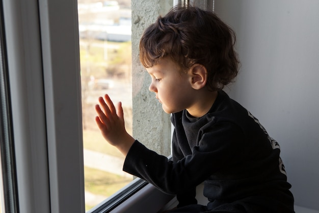 Quarantine during a coronavirus pandemic. . the child stands on the windowsill and looks at the empty city through the window. dreams to go out and breathe fresh air.